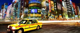 A Tokyo taxi driving through the neon-lit streets of Shinjuku,