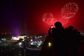 South Koreans take pictures of fireworks during a countdown event to celebrate the New Year at Imjingak peace park, Paju, South Korea
